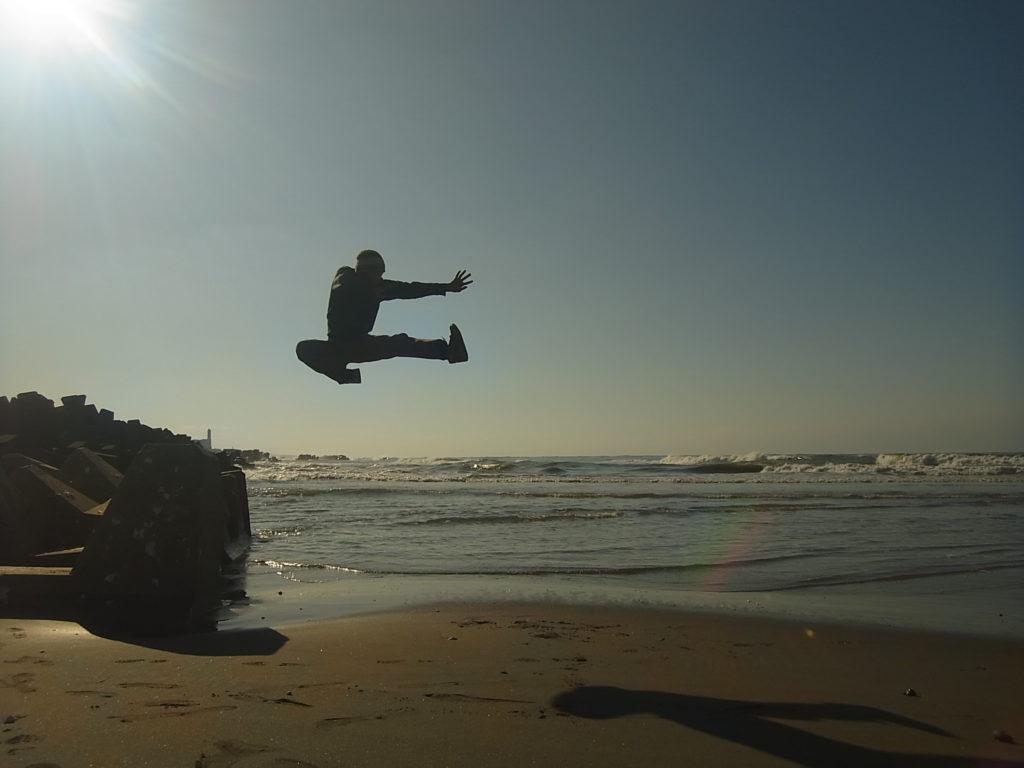海をバックに、高さのある飛び蹴り