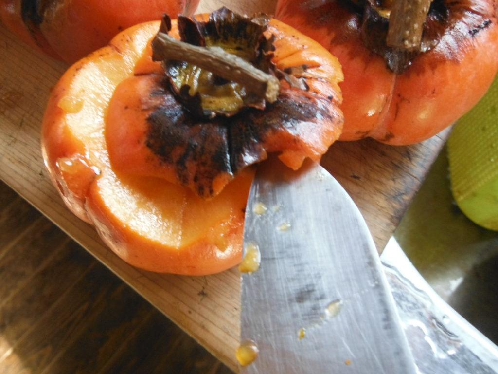 熟した柿のヘタを包丁で切る。