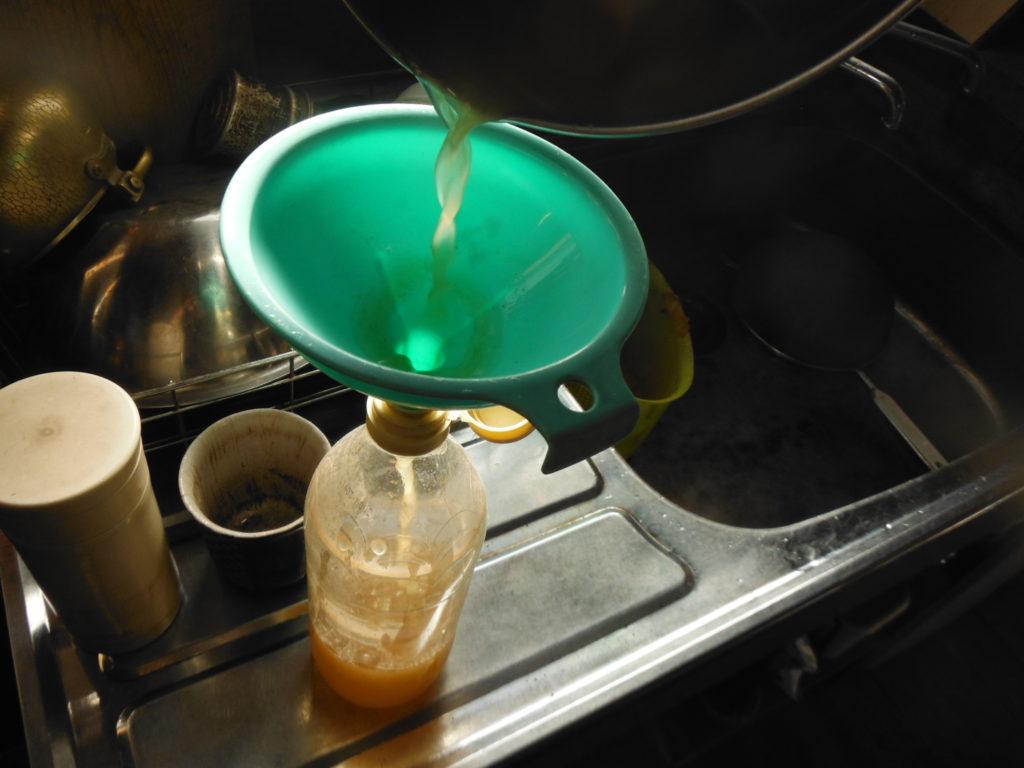濾した柿酢を漏斗でビンに詰めていく。
