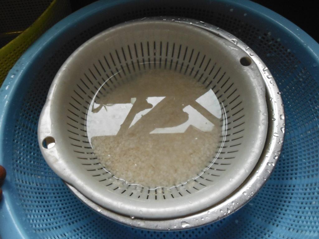 ザルに白米を入れて、水で洗う。