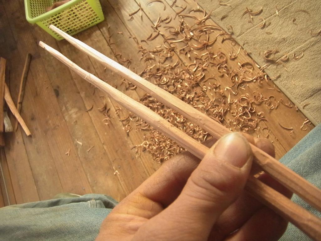 小刀で削られた木のお箸を手で持つ。