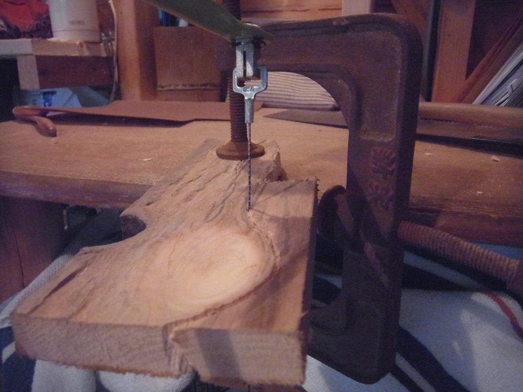 クランプで固定された板を、糸鋸で切る。