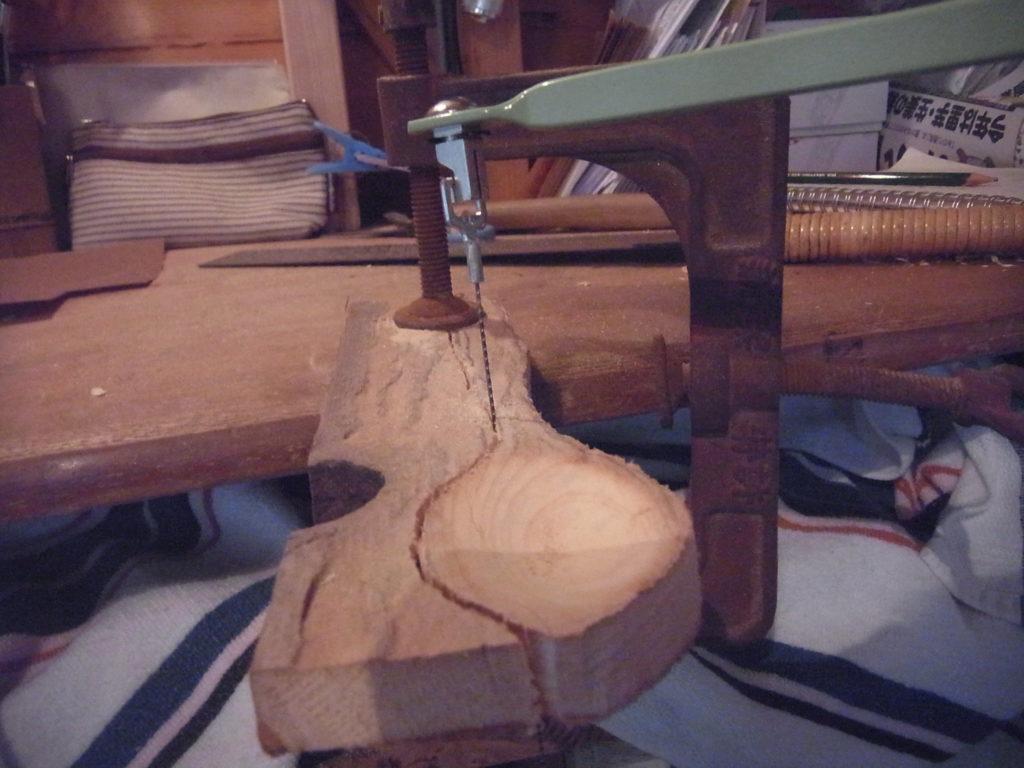 クランプで固定された板をスプーンの形に切っていく。