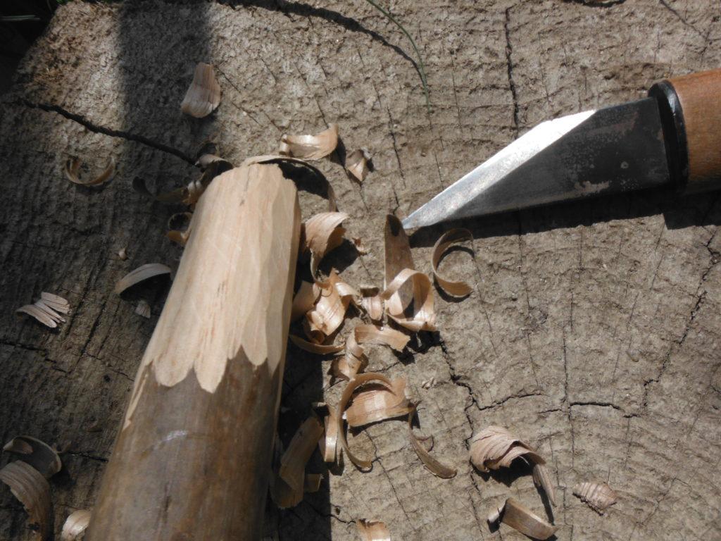 鍬の柄を小刀で削る。