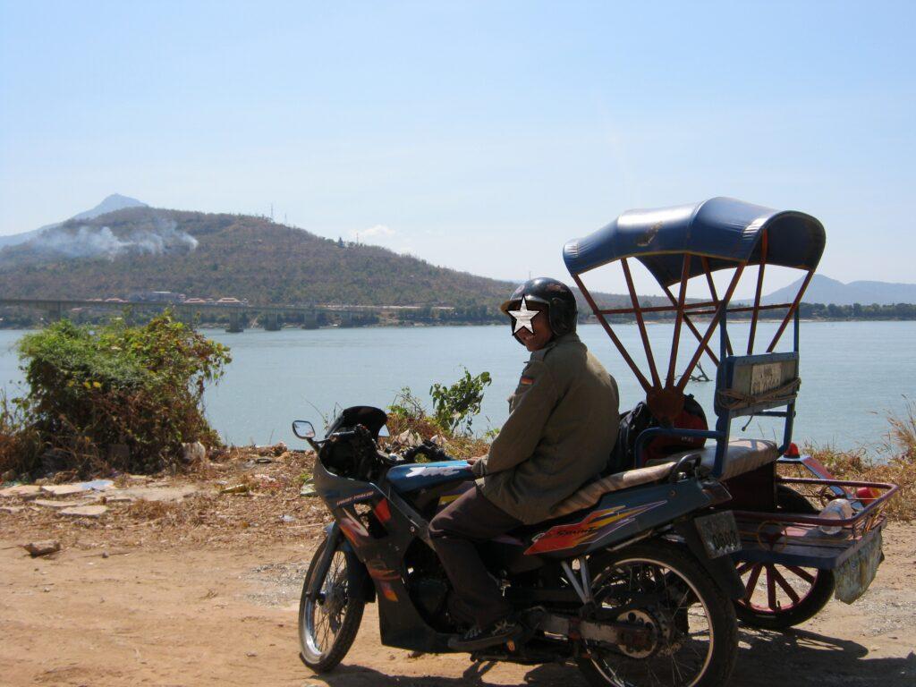 メコン川をバックに、バイクタクシー。