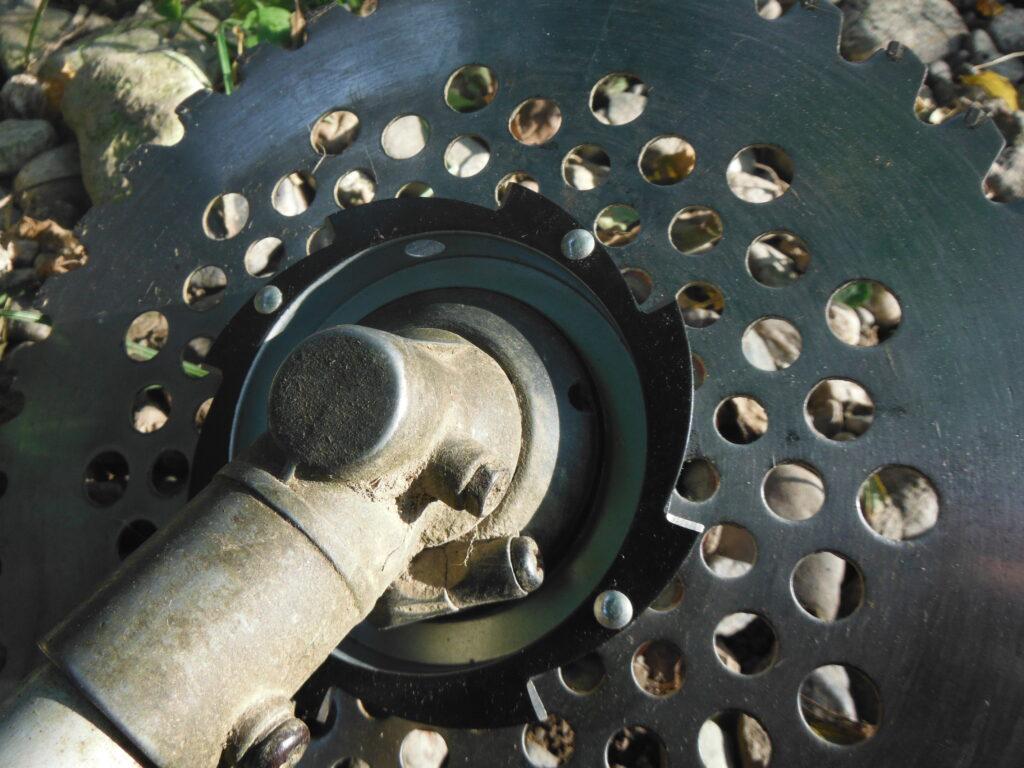 刈払い機に、まき草防止カッターを取り付ける。